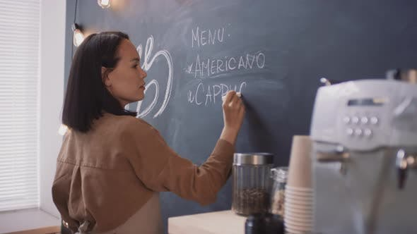Thumbnail for Asian Coffeeshop Worker Writing On Blackboard