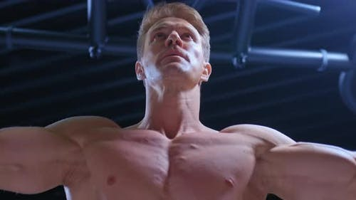 Portrait of a Young Muscular Bodybuilder Doing Convergence of Hands on the Upper Block Strength