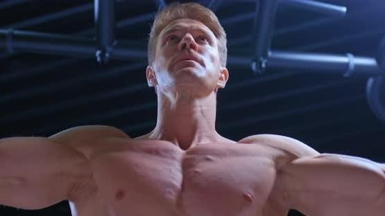 Porträt eines jungen muskulösen Bodybuilders, der die Konvergenz der Hände auf der oberen Blockstärke macht