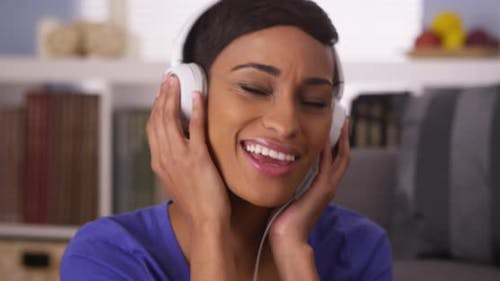 Pretty black woman listening to music with headphones