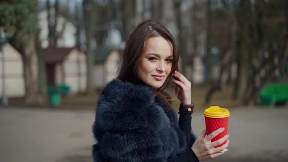 Thumbnail for Beautiful woman with a plastic cup of coffee in the park