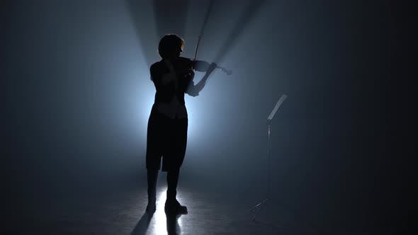 Thumbnail for Girl Plays the Violin and Looks at the Music Stand in the Dark