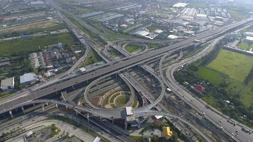 Aerial View of Highway Road Interchange with Busy Urban Traffic Speeding on Road