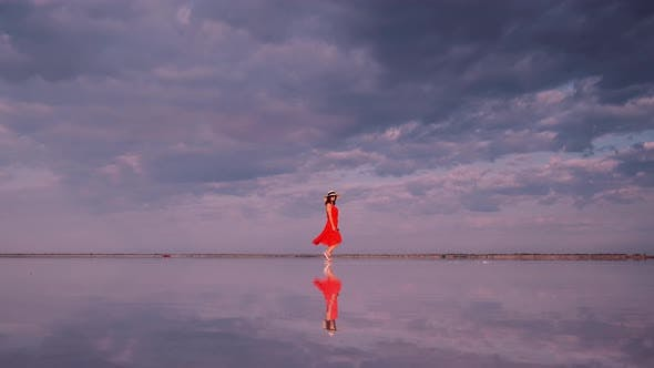 Thumbnail for Young Woman in a Waving Dress Walks Along a Pink Lake in Which Clouds Are Reflected.