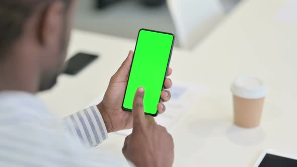 Rear View of African Man Using Laptop with Green Chroma Key Screen