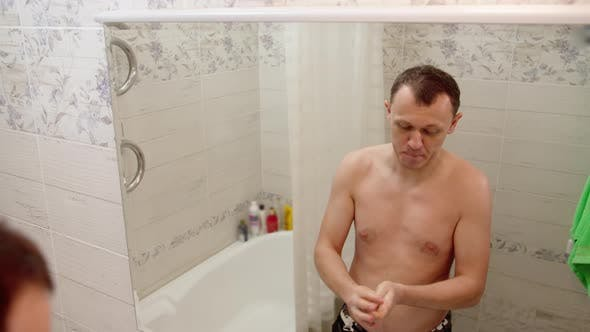 A Man Washes His Hands with Soap and Wipes Them with a Towel
