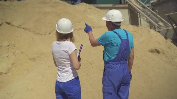 Thumbnail for Back View of Male Worker and Female Inspector Standing in Front of Stack of Yellow Sand and Talking