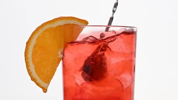 Thumbnail for Mixing pink cocktail in glass over white