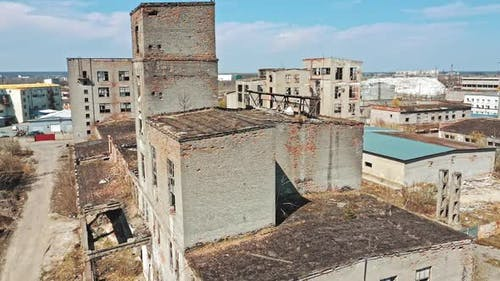 Flying over the desolate place with many abandoned buildings in a city