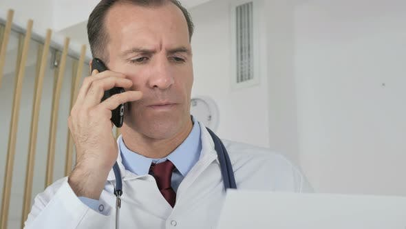 Thumbnail for Doctor Talking on Phone with Patient Discussing Medical Report