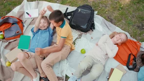 Schoolchildren Lying on Blankets in Park after School