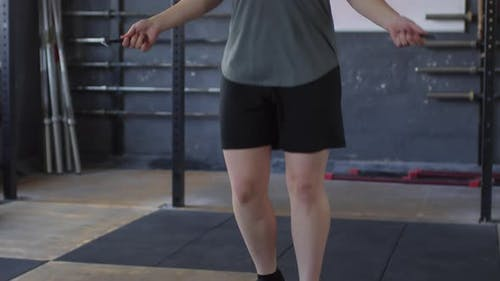 Female Athlete Jumping Rope and Looking at Camera in Gym