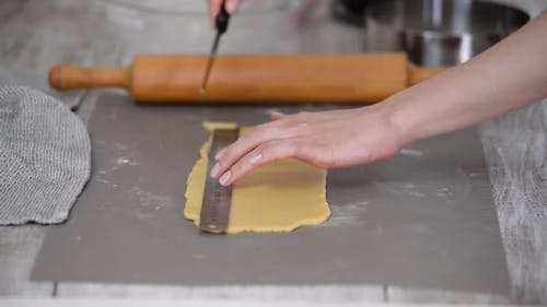 Cutting Raw Dough in Flour with a Knife