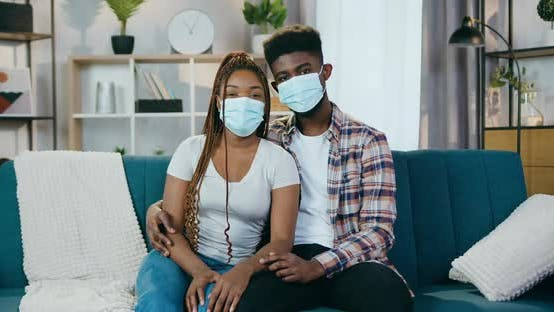African American Couple Sitting on Couch in Medical Masks