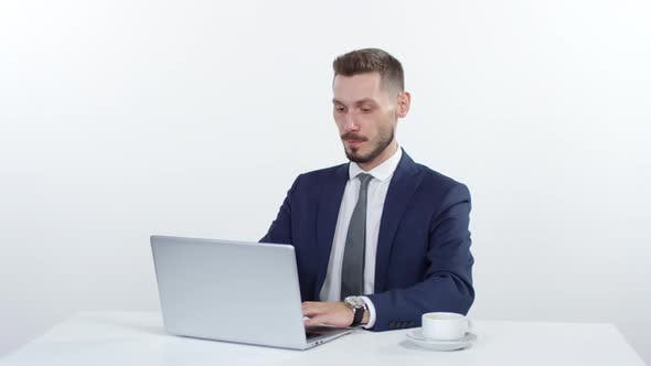 Thumbnail for Businessman Working on Laptop and Drinking Coffee