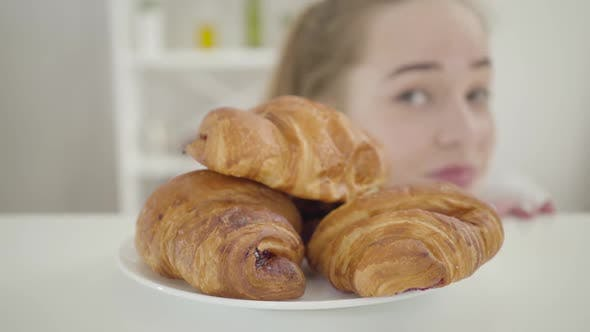 Blurred Caucasian Girl Looking Around and Biting Fresh Delicious Crusty Croissant