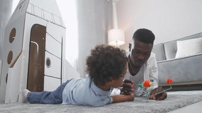 African Father and Son Play in the Living Room at Home Man Lying on the Floor with Her Son Boy