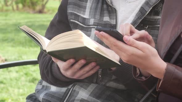Thumbnail for Couple Is Sitting On A Bench In The Park In The Spring And Reading An Interesting Book