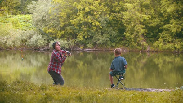 Thumbnail for Two Brothers on Fishing - Big Brother Throws Fishing Rod in the Lake