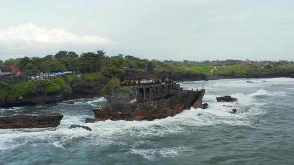 Strong Ocean Waves Crashing Into Rocky Cliff with Tanah Lot Temple in Bali Indonesia