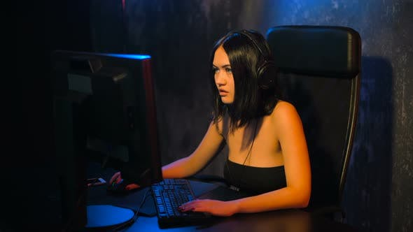Serious Woman Gamer Playing Online Game on a Pc Computer Wearing Headset and Talking with a Team