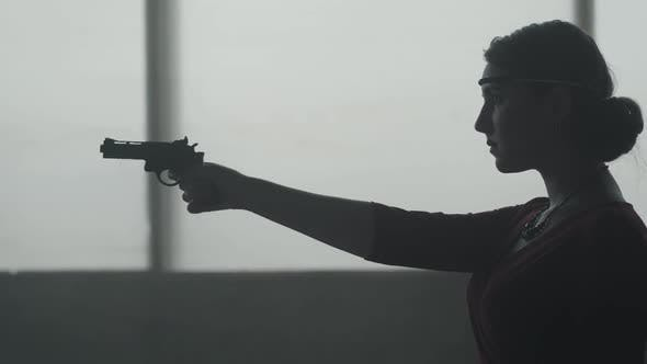 Thumbnail for Confident Woman in Stylish Red Dress Is Aiming a Pistol in an Abandoned Dusty Building