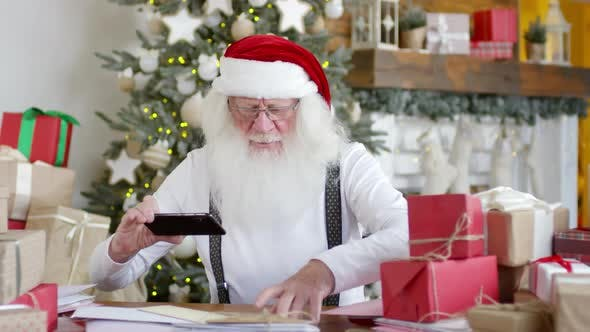 Thumbnail for Santa Claus Photographing Letters with Smartphone