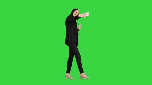 Thumbnail for Smiling Arab Woman in Hijab Taking Selfies on Her Mobile Phone As She Walks on a Green Screen