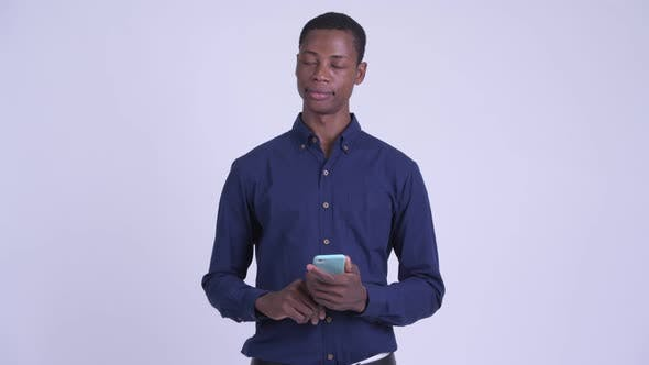 Thumbnail for Young Happy African Businessman Thinking While Using Phone