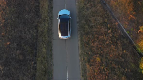 Thumbnail for Aerial Shot of Electrical Car Driving Through Country Road at Summer Evening. Modern Vehicle Passing