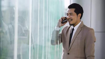 happy successful young business man using a smartphone
