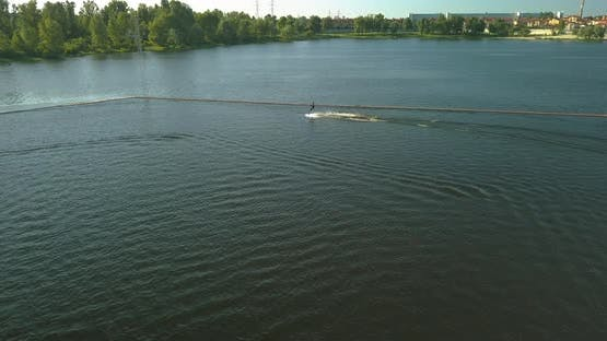 Aerial View of the Anchorage of the Cable Car Wake Park and an Athlete Cutting Through the Water on