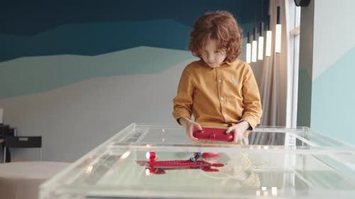 Red-haired Boy Controlling Robo Boat with Joystick