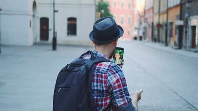 Back View of Tourist Making Video Call on Smartphone