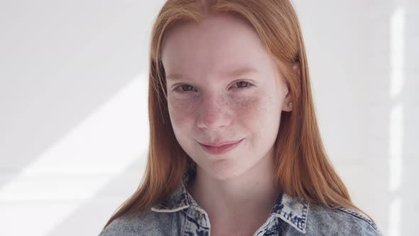 Happy Ginger Teenage Girl with Freckles Smiling Against White Wall