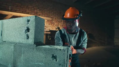 Black Contractor Drilling Brick Wall in Dark Room
