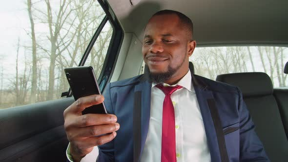 Cheering Black Businessman with Phone Celebrating Success in Car