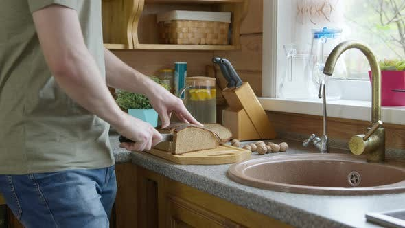 Thumbnail for Caucasian Handsome Man Cuts Bread Into Pieces with a Sharp Kitchen Knife on a Oak Wooden Board.