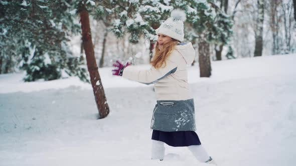 Thumbnail for Cheerful Girl in a White Down Jacket and Purple Gloves are Throwing Snowballs in the Park