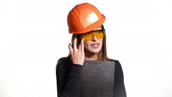 Thumbnail for Woman in an Orange Helmet and Protective Eyeglasses is Talking and Holding a Pen and Folder