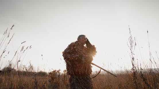 Thumbnail for Hunter in Hunting Equipment with Gun Relaxing, Tugs a Hat in the Field Foggy Morning Sunrise Light