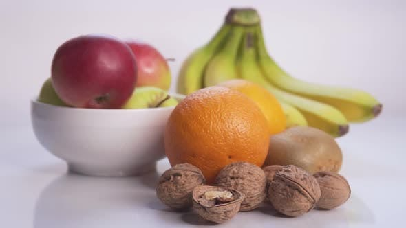 Thumbnail for Girl Lays Fruits and Nuts on the Table With Slow Motion