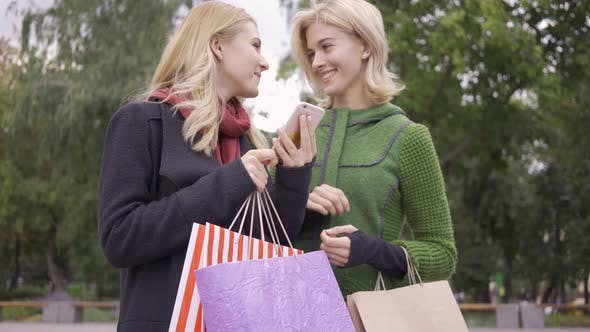 Thumbnail for Two Beautiful Blond Girlfriends Standing on the Street with Shopping Bags Looking at Cellphone