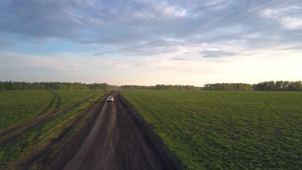 Thumbnail for White Car Passes Black Car Standing on Dirty Roadside
