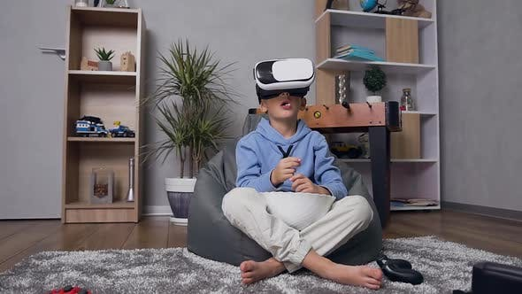 Little Boy in Virtual Reality Headset Sitting on Inflatable Armchair Enjoying Video