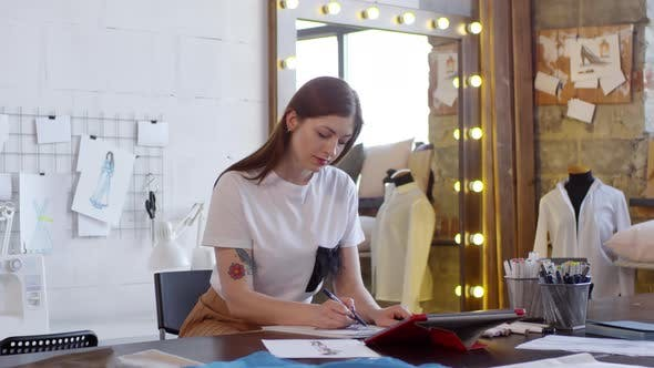 Young Female Designer Drawing Fashion Sketch in Sewing Workshop