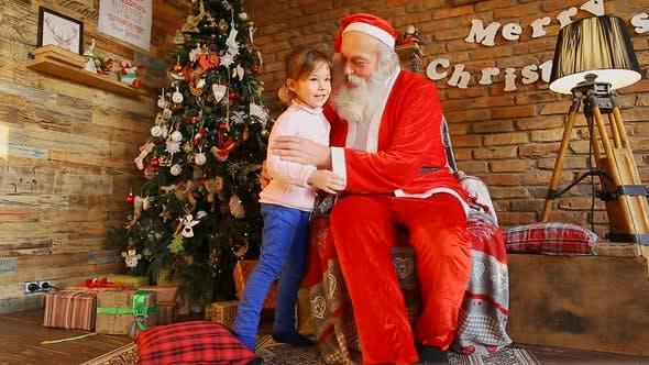 Thumbnail for Little Girl Hugs  Santa and Smiles Happily.