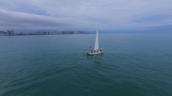 Thumbnail for Boat Swimming Under Sails Across Sea Against Batumi, Couple Standing at Bow
