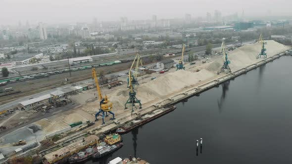Aerial view of cargo port cranes near a pile of sand with ships, scows and barges