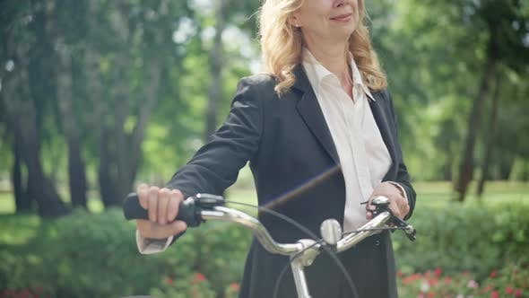 Unrecognizable Smiling Caucasian Middle Aged Businesswoman Walking in Sunlight with Bicycle in